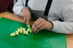 Children dicing vegetables in Rhyl Kitchen Classroom